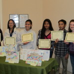 The teens who won the art contest show their works.